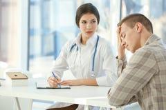 Junger deprimierter Mann in Doktor ` s Büro Lizenzfreies Stockbild
