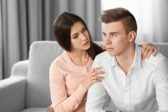 Junger deprimierter Mann mit Freundin zu Hause Lizenzfreie Stockfotografie