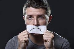 Junger deprimierter Mann verlor in der Traurigkeit und in Sorge halten Papier mit traurigem Mund im Krisenkonzept Stockfotografie