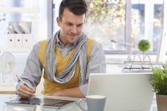 Junger Designer, der das Zeichnungsauflagelächeln verwendet Lizenzfreies Stockbild