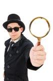 Junger Detektiv im schwarzen Mantel, der das Vergrößern hält stockfotografie