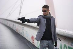 Junger Detektiv oder Polizist oder Gangster, die a abfeuern lizenzfreie stockfotografie