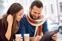 Junger die sprechende Mann und Frau, haben sie Spaß, sie haben in ihren Händen die Tablette Sie trinken Kaffee oder Tee stockfotos