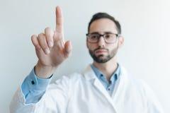 Junger Doktor, der durch einen Finger drückt Plan für eine medizinische Platte des futuristischen Schirmes stockbild