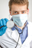Junger Doktor, der ein Stethoskop hält Stockbilder