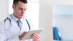 Junger Doktor, der einen Tabletten-PC verwendet stock video footage