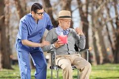 Junger Doktor, der einen traurigen Senior in einem Park tröstet Lizenzfreies Stockfoto