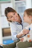 Junger Doktor, der kleines Mädchen mit Stethoskop überprüft Lizenzfreie Stockfotografie