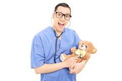 Junger Doktor, der medizinische Kontrolle auf einem Teddybären tut Stockfotos