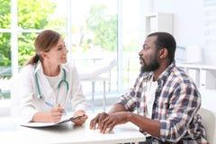 Junger Doktor, der mit afro-amerikanischem Patienten spricht stockbild