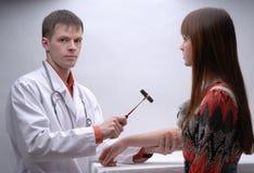 Junger Doktor, der Nervensystem des Patienten prüft Stockfoto