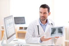 Junger Doktor, der Radiographie auf einer Tablette zeigt Lizenzfreie Stockfotos