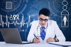 Junger Doktor, der vor Laptop arbeitet Stockbild