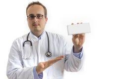 Junger Doktor, der weißen Kasten darstellt Lizenzfreies Stockfoto