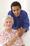 Junger Doktor, der zu Hause Hände älterer Dame hält Stockbilder