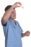 Junger Doktor des männlichen Kursteilnehmers, der eine Probe überprüft stockbild