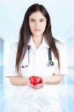 Junger Doktor Gently Holds ein Herz Stockfotos