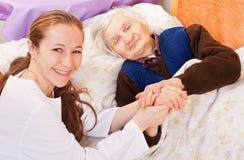 Junger Doktor hält die älteren Frauenhände an Stockfoto