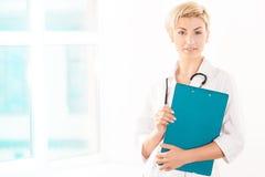 Junger Doktor im weißen Mantel mit grüner Tablette Lizenzfreies Stockfoto