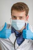 Junger Doktor machend Daumen up Zeichen Stockbild