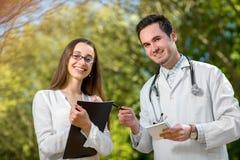 Junger Doktor mit dem jungen und hübschen behilflichen Sprechen stockfoto