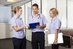 Junger Doktor mit zwei Krankenschwestern Stockfotos