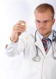 Junger Doktor sehen ein Prüfunggefäß Stockbild