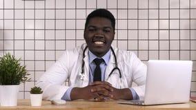 Junger Doktor an seinem Arbeitsplatzlächeln stockfotos