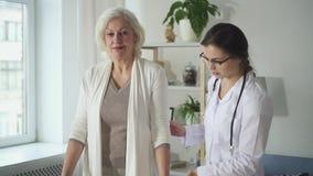 Junger Doktor stellt zur weiblichen älteren geduldigen Gesundheitswesenübung dar stock video