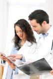 Junger Doktor und Krankenschwester, die Radiographie analysiert Lizenzfreie Stockfotos