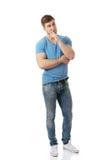 Junger durchdachter Mann mit dem Finger unter Kinn Stockfotos
