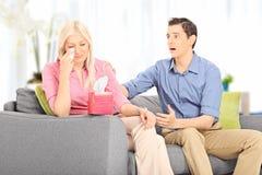 Junger Ehemann, der seine traurige Frau gesetzt auf Sofa tröstet Stockbilder