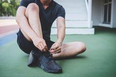 Junger Eignungsathletenmann, der auf der Stra?enbahn, ?bungstraining Wellness und L?ufer binden Spitzee mit Kopienraum vor Lauf l stockfotografie