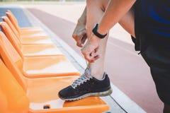 Junger Eignungsathletenmann, der auf der Stra?enbahn, ?bungstraining Wellness und L?ufer binden Spitzee mit Kopienraum vor Lauf l lizenzfreie stockbilder