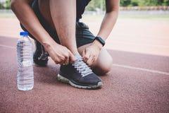 Junger Eignungsathletenmann, der auf der Stra?enbahn, ?bungstraining Wellness und L?ufer binden Spitzee mit Kopienraum vor Lauf l lizenzfreies stockfoto