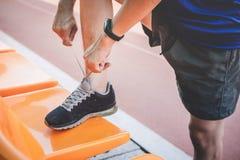 Junger Eignungsathletenmann, der auf der Stra?enbahn, ?bungstraining Wellness und L?ufer binden Spitzee mit Kopienraum vor Lauf l stockbilder