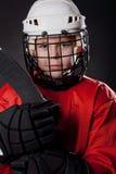 Junger Eishockeyspieler auf dunklem Hintergrund Stockfoto