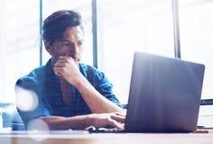 Junger eleganter Bankwesenfinanzanalytiker, der im sonnigen Büro auf Laptop beim Sitzen am Holztisch arbeitet Geschäftsmann lizenzfreies stockfoto