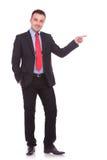 Junger eleganter Geschäftsmann, der mit einer Hand zeigt Stockfotos