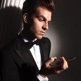 Junger eleganter Mann, der unten beim Genießen einer Zigarette schaut Stockfotografie