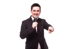 Junger eleganter Unterhaltungsmann, der das Mikrofon spricht mit dem Zeigen des Fingers hält Stockfoto