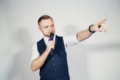 Junger eleganter Unterhaltungsmann, der das Mikrofon spricht mit dem Zeigen des Fingers hält Getrennt auf grauem Hintergrund Stockfotografie