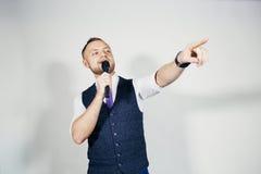 Junger eleganter Unterhaltungsmann, der das Mikrofon spricht mit dem Zeigen des Fingers hält Getrennt auf grauem Hintergrund lizenzfreie stockbilder