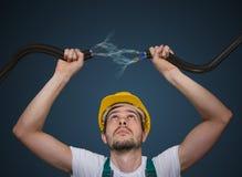 Junger Elektriker hält Kabel in den Händen und in der Verbindung sie Blitz und Strom herum Lizenzfreie Stockbilder