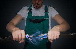 Junger Elektriker hält Kabel in den Händen und in der Verbindung sie Blitz und Strom herum Stockfotos
