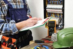 Junger Elektrikertechniker bei der Arbeit über eine elektrische Platte Lizenzfreie Stockfotos