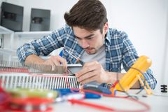 Junger Elektrogerätversammlungsteilnehmer bei der Arbeit lizenzfreies stockbild