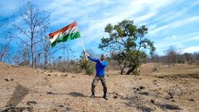 Junger enthusiastischer indischer Mann, der eine dreifarbige, indische Flagge hält Lizenzfreie Stockbilder