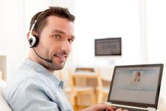 Junger entspannter Mann, der auf Internet Video-nennt Lizenzfreie Stockbilder