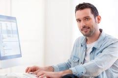 Junger entspannter Mann, der Computer verwendet Stockfotos